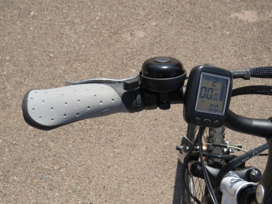 The left side of the handlebars: the front brake lever, a bell, and the e-bike display