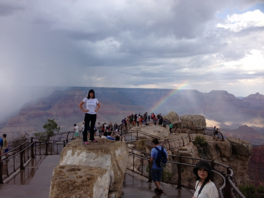 Susan shines in the spotlight of a rainbow that formed in the Canyon