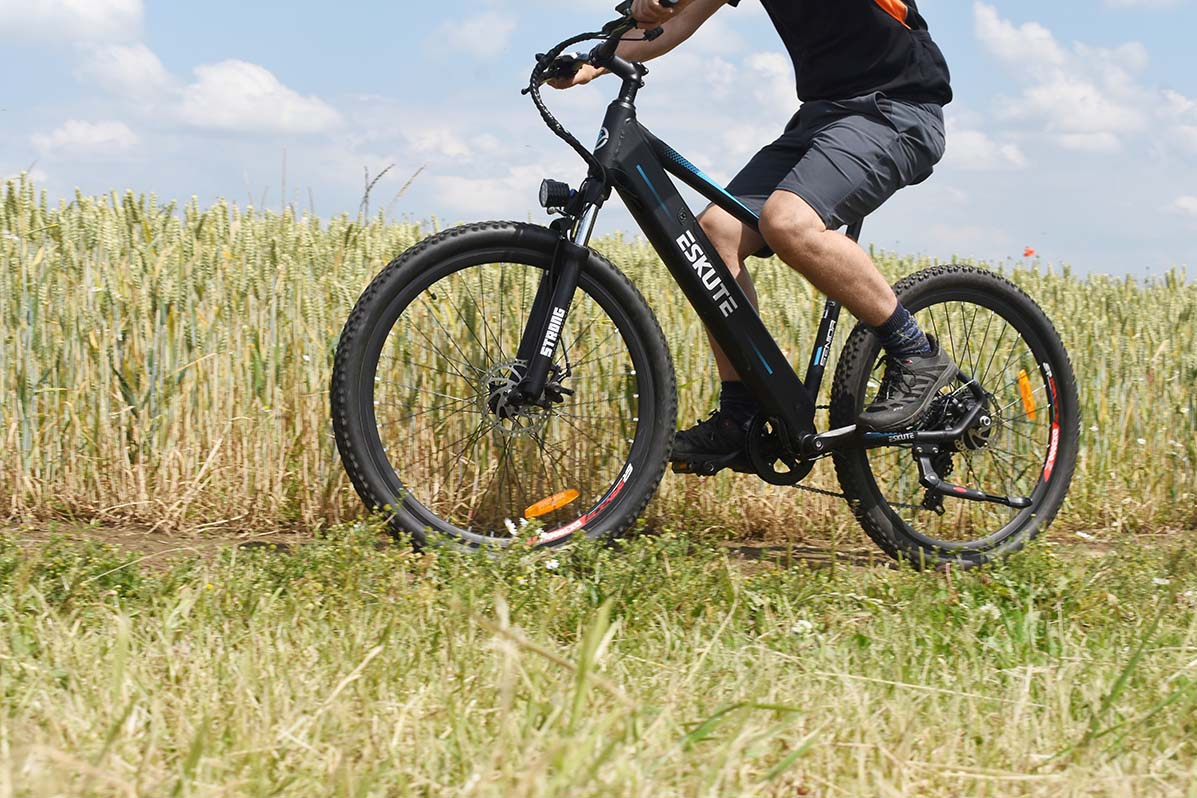 eskute voyager electric bike review riding in meadow